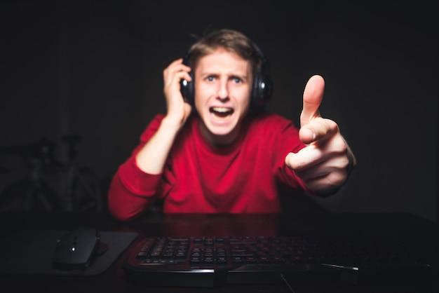Joueur agressif joue à des jeux en ligne à la maison sur un ordinateur