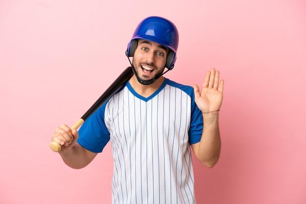 Joueur de baseball avec casque et batte isolé sur fond rose saluant avec la main avec une expression heureuse