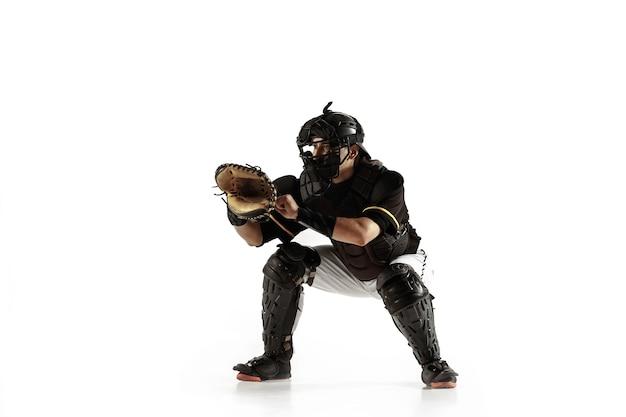 Joueur de baseball, lanceur dans un uniforme noir pratiquant et entraînement isolé sur un mur blanc. jeune sportif professionnel en action et en mouvement. mode de vie sain, sport, concept de mouvement.