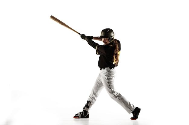 Joueur de baseball, lanceur en uniforme noir pratiquant et s'entraînant isolé sur un mur blanc. jeune sportif professionnel en action et en mouvement. mode de vie sain, sport, concept de mouvement.