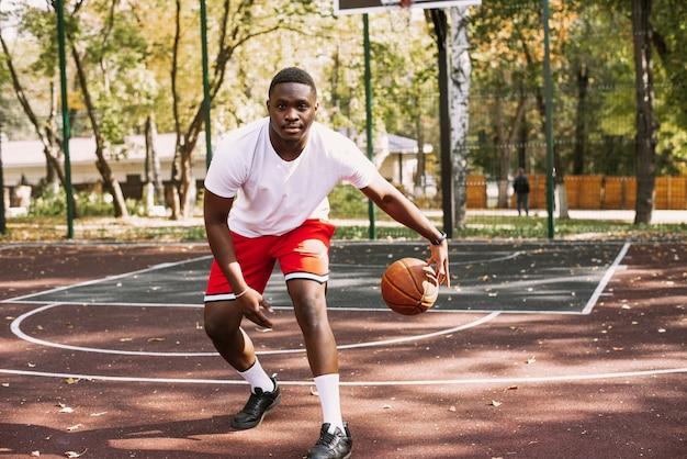 Joueur de basket-ball afro-américain sur un terrain de sport extérieur jouant avec un ballon. faire du sport dans la rue.