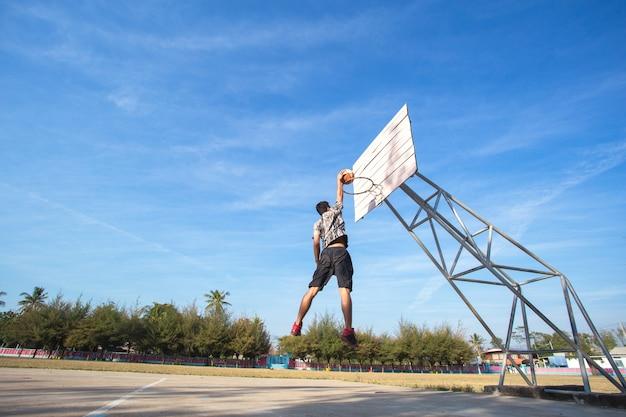 Joueur de basket-ball faisant du slam dunk