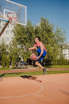 Joueur de basket-ball faisant un tour en face du panneau arrière