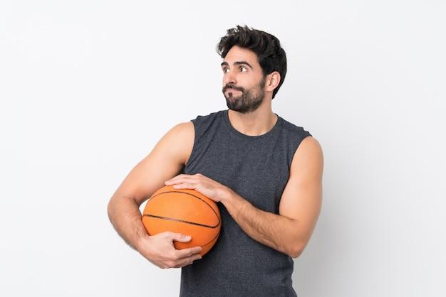Joueur de basket-ball homme avec barbe sur mur blanc isolé faisant des doutes geste tout en soulevant les épaules