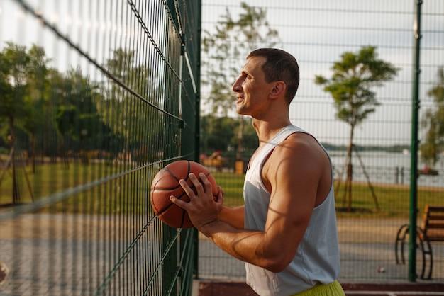 Joueur de basket-ball masculin avec ballon debout à la clôture grillagée sur le terrain extérieur