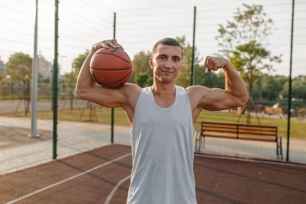 Joueur de basket-ball masculin avec ballon montre ses muscles sur le terrain extérieur, vue de face.