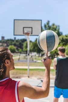 Joueur de basket-ball tourne la balle sur son doigt