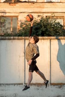 Joueur de basket urbain sur le côté, sautant