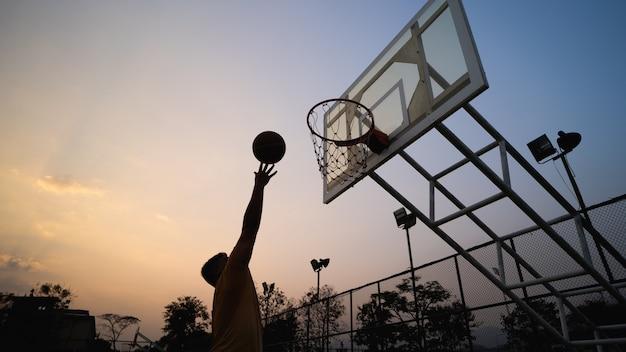 Joueur de basketball s'entraînant et s'entraînant à l'extérieur sur le terrain