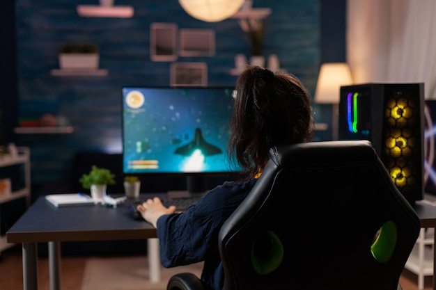Joueur compétitif à la recherche d'un ordinateur puissant jouant à un jeu vidéo de tir spatial pour un tournoi en direct tard dans la nuit dans un home studio. joueur professionnel en streaming de nouveaux graphismes de jeux vidéo en ligne