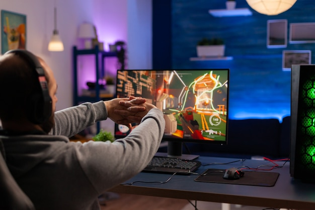 Joueur compétitif s'étirant après avoir joué à des jeux vidéo numériques sur un ordinateur puissant à l'aide d'un casque pro. cyber-streaming en ligne lors d'un tournoi de jeu dans une salle avec des néons