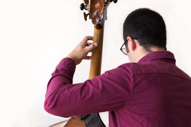 Joueur de contrebasse professionnel. prise de photos en studio. blanc