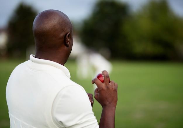 Un joueur de cricket prêt à lancer la balle