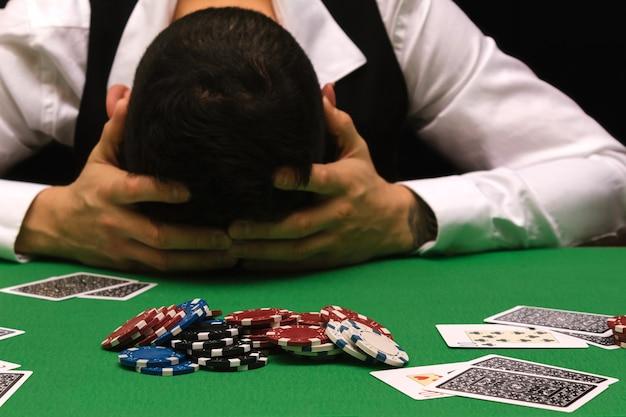 Un joueur dévasté perdant beaucoup d'argent en jouant au poker dans un casino, une dépendance au jeu. divorce, perte, ruine, dette, concept de ludopata.