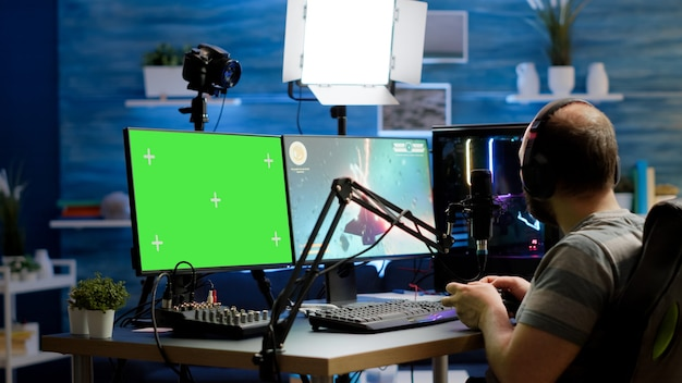 Joueur diffusant des jeux vidéo en ligne sur un ordinateur professionnel puissant avec écran vert, maquette, affichage d'incrustation de chrominance. streamer jouant au jeu de tir spatial sur un bureau isolé tenant un contrôleur sans fil