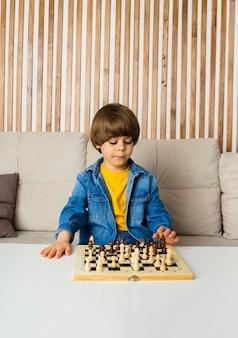 Joueur d'échecs petit garçon aux cheveux bruns et vêtements en jean est assis sur le canapé et joue aux échecs dans la chambre