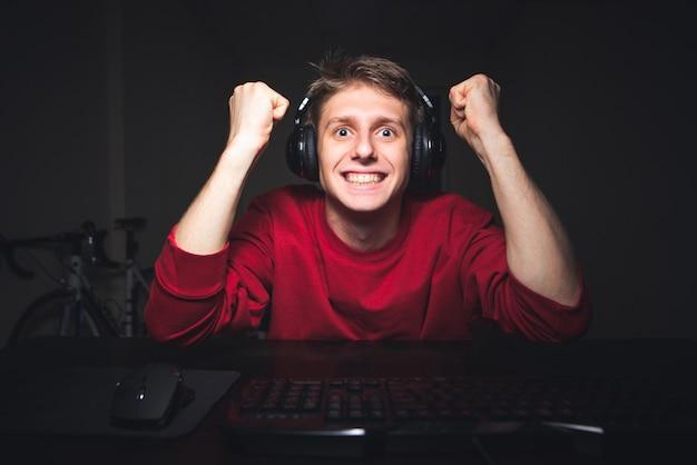 Joueur émotionnel est assis à la maison dans la chambre la nuit et joue à des jeux vidéo