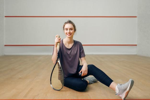 Joueur féminin avec raquette de squash assis sur le sol. fille sur la formation de jeu, passe-temps sportif actif sur le terrain