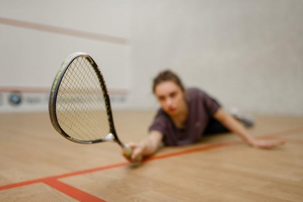Joueur féminin avec raquette de squash se trouve sur le sol. fille sur la formation de jeu, passe-temps sportif actif sur le terrain