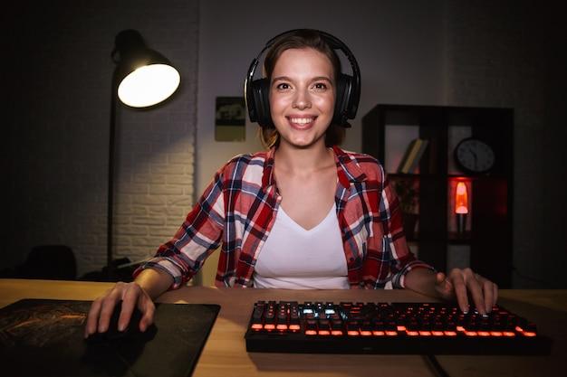 Joueur de femme excité assis à la table, jouant à des jeux en ligne sur un ordinateur à l'intérieur, célébrant le succès