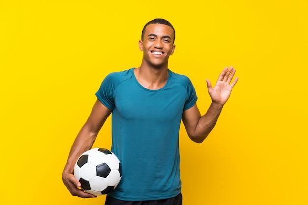 Joueur de football afro-américain homme saluant avec la main avec une expression heureuse