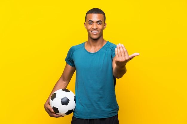 Joueur de football afro-américain invitant à venir avec la main. heureux que tu sois venu