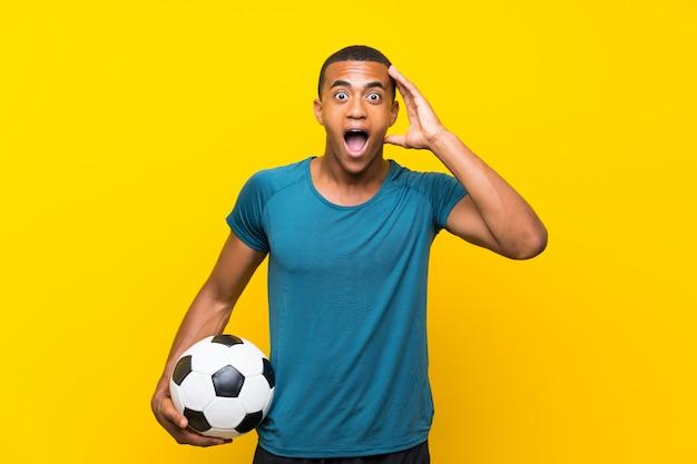 Joueur de football afro-américain avec surprise et expression faciale choquée