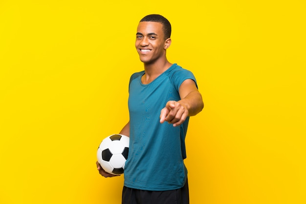 Un joueur de football afro-américain vous montre du doigt avec une expression confiante