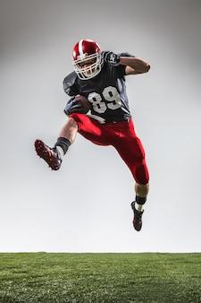 Le joueur de football américain en action sur l'herbe verte et le fond gris.