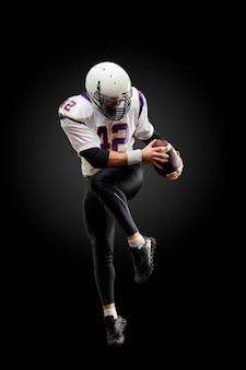 Joueur de football américain dans un saut avec un ballon sur un fond noir
