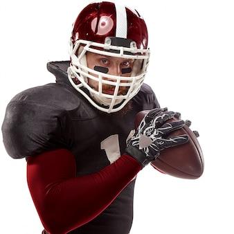 Joueur de football américain posant avec ballon sur blanc