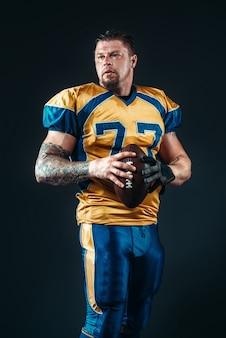Joueur de football américain pose avec ballon dans les mains