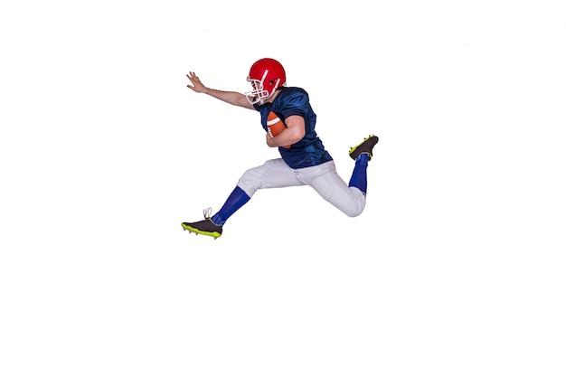 Joueur de football américain, sautant avec la balle