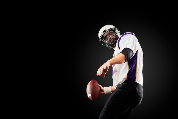 Joueur de football américain sportif sur fond noir. sport .