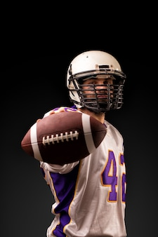 Joueur de football américain tenant le ballon dans ses mains devant la caméra. concept football américain, motivation, espace noir