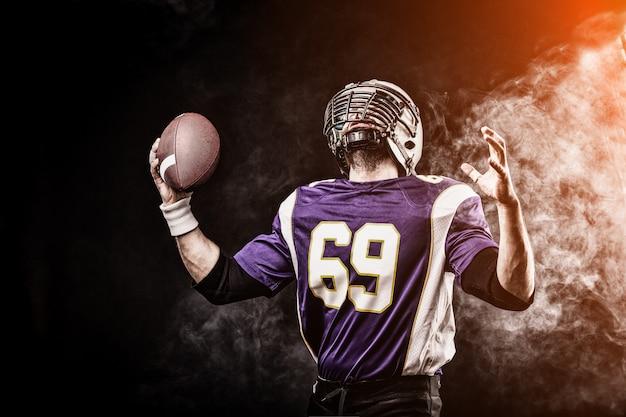 Joueur de football américain tenant le ballon dans ses mains en fumée. espace noir, espace copie. le concept du football américain, la motivation, l'espace de copie