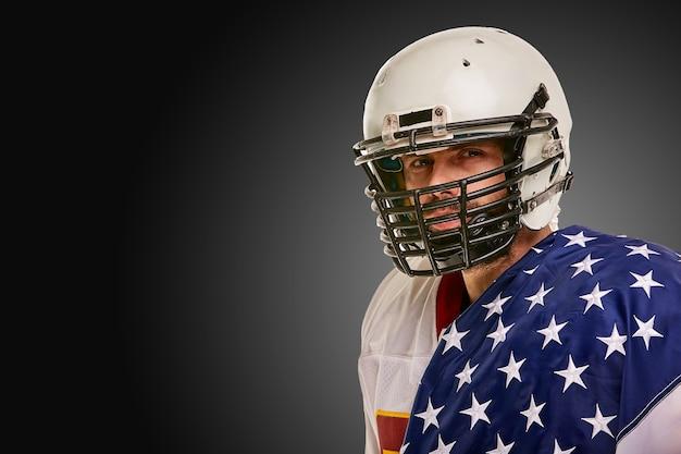 Joueur de football américain avec uniforme et drapeau américain fier de son pays sur fond noir.