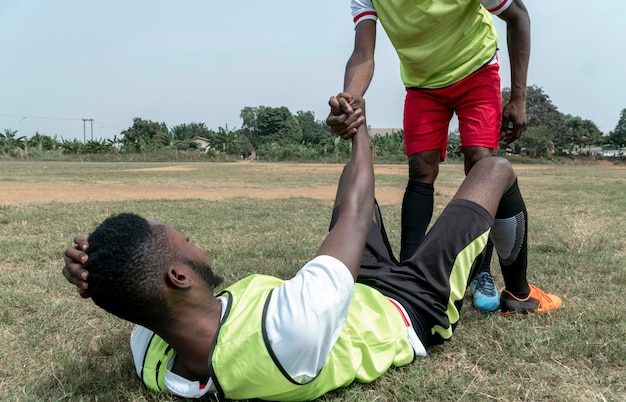 Joueur de football assis sur le terrain