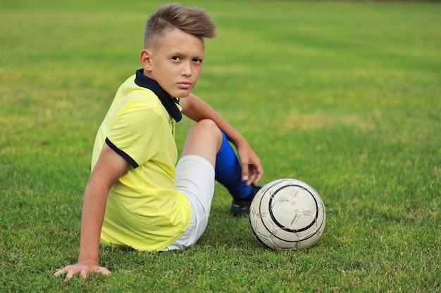 Joueur de football beau garçon assis sur le terrain de football
