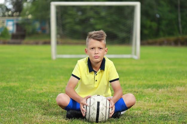 Joueur de football beau garçon dans un t-shirt jaune et gntra bleu se trouve sur le terrain de football