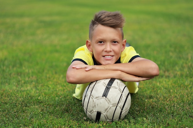 Joueur de football beau garçon se trouve sur le terrain de football avec le ballon