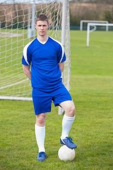 Joueur de football en bleu posant avec la balle sur terrain