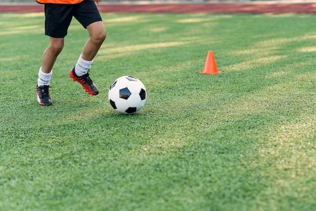 Joueur de football botter le ballon sur le terrain. joueurs de football en séance d'entraînement. gros plan des pieds de footballeur