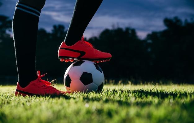 Joueur de football donnant un coup de pied au ballon de football au point de coup franc.