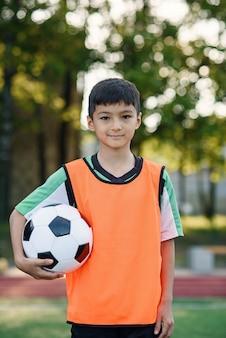 Joueur de football fatigué en gilet orange tient le ballon en main après l'entraînement