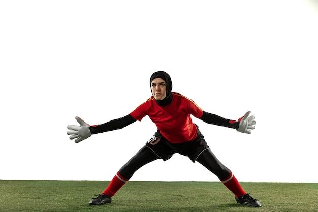 Joueur de football ou de football féminin arabe, gardien de but sur fond de studio blanc. jeune femme attraper le ballon, s'entraîner, protéger les objectifs en mouvement et en action. concept de sport, passe-temps, mode de vie sain.