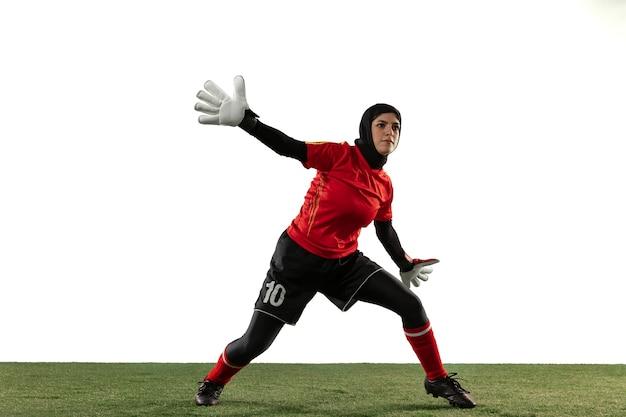 Joueur de football ou de football féminin arabe, gardien de but sur fond de studio blanc.