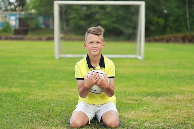 Joueur de football garçon est assis sur le terrain de football dans le contexte de l'objectif avec le ballon