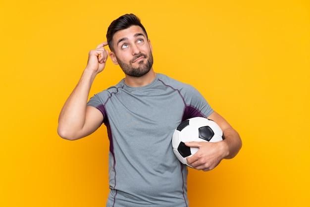 Joueur de football homme sur mur isolé ayant des doutes et avec une expression de visage confuse
