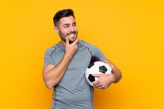 Joueur football, homme, sur, mur isolé, regarder côté